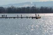 Fotografie Menschen ar Holz Netz am See