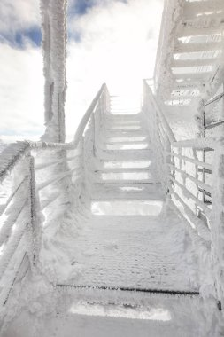 Stairs and rail, completely covered with ice crystals, strong sun back light in background. Freezing winter.