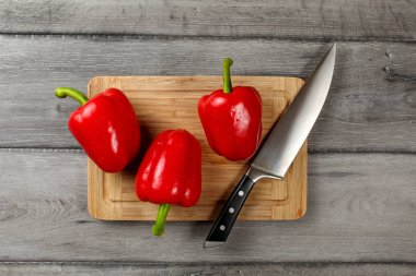 Table top view - three bright red bell peppers, water drops, with chefs knife on chopping board, with rustic gray wood desk under.