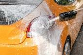 Žluté auto umýt v myčka, mýdlo ad pěna postřik kapky na slunce svítí zadní a zadní světlo.