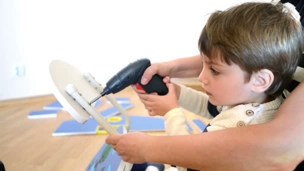 Little Boy using diy tool at home, helped by parent