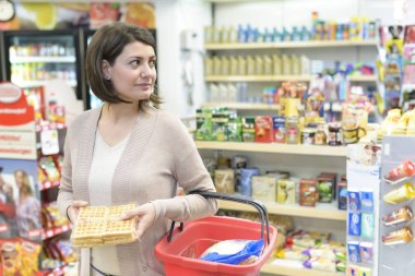 Pretty woman with shopping basket choosing products in supermarket