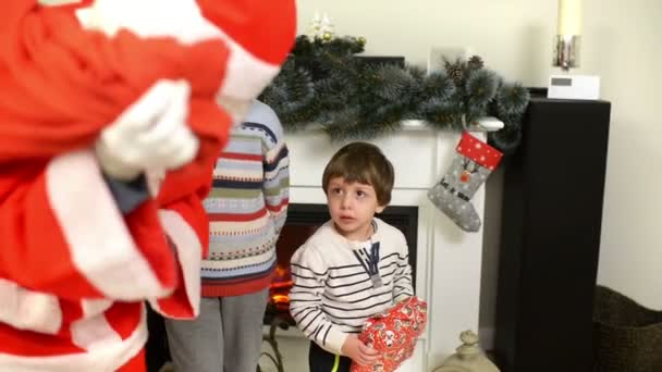 Santa Claus giving presents to cute children near fireplace and Christmas tree