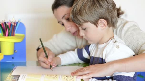 Matka pomáhá její roztomilé dítě aby kresby
