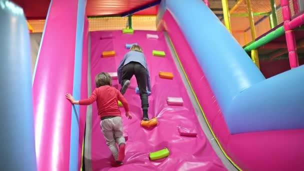 Lustige Jungs, die auf aufgeblasenem Rutsch spielen, Indoor-Spielplatz