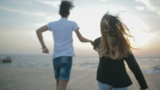 girlfriend and boyfriend with joined hands running on boardwalk against sunset over sea