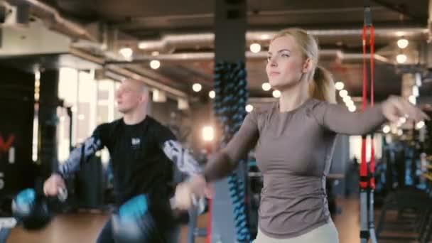 koncentrovaná mladá žena a muž se svaly dřepy aktivně s závažími v profesionální crossfit tělocvičny zblízka