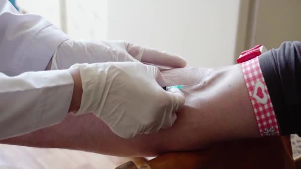 Takes a blood sample for tests. Hand of doctor injects a syringe into a vein of patient. Arm of medic taking blood. Close up