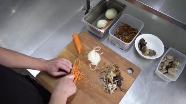 Profesionální kuchaři v restauraci nebo v kuchyni v hotelu, šéfkuchař kusy mrkve na dřevěném prkénku, pohled shora
