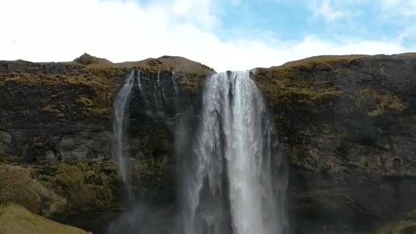 Voda, která padá jako stěna opona u vodopádu Skogafoss na Islandu.