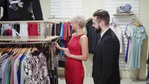 Ukazující oblečení manželovi. Krásná blonďatá stylová, zářivě zářící žena, která ukazovala černé šaty manželovi v obchodě s oděvy