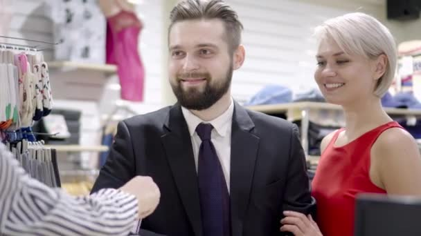 sale, consumerism, shopping and people concept - happy couple with credit card at clothing store in mall