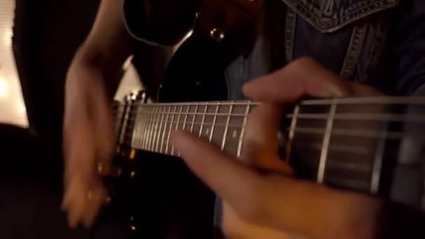 Közelről lövés két férfi játszik elektromos gitárt a színpadon éjjel