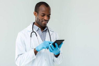 Digital advancements. Professional afro american doctor using his tabet against white background