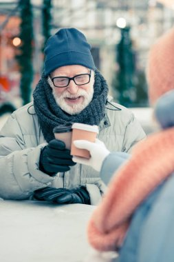 Positive aged man in warm clothes relaxing outdoors in winter day and clanging cups of coffee with his friend