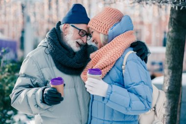 Romantic atmosphere of a senior man gently hugging his wife outdoors while drinking coffee on winter day with her