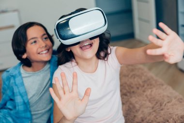 Mirthful boy smiling while sitting near the emotional girl and watching her using modern virtual reality glasses