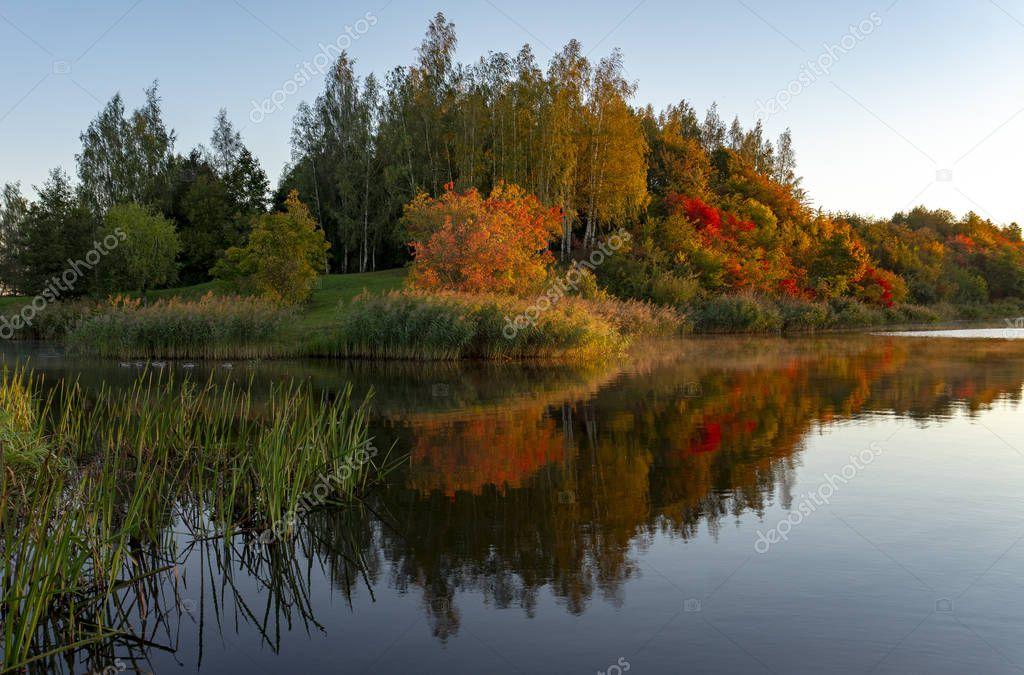Fall season start idyllic lake reflections of fall foliage. Colorful autumn foliage casts its reflection on the calm waters