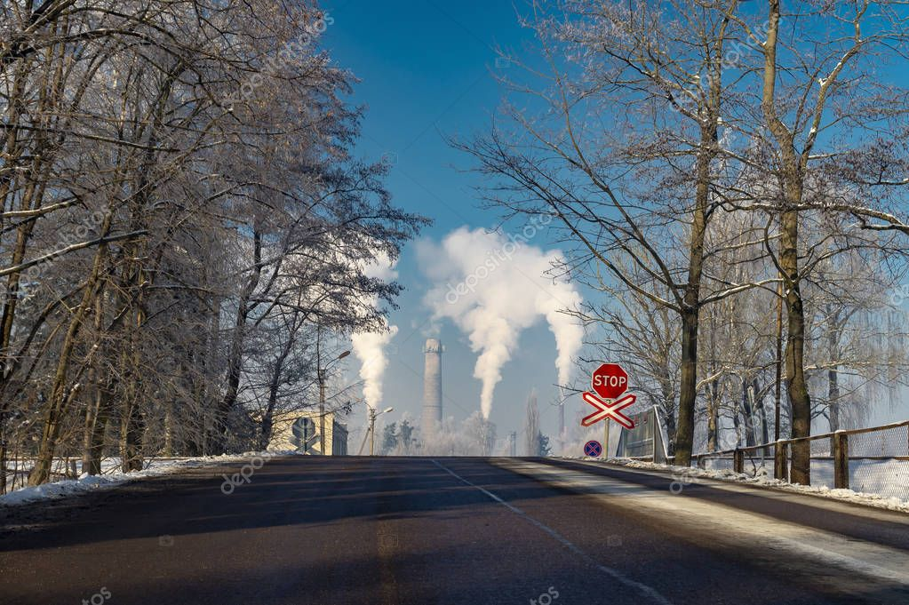 View down a winter street of smoking chimney stacks in an industrial district in a concept of pollution of the atmosphere