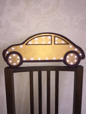 Beautiful night light in the form of a car of golden color with dark brown edging. Decorating a little boy's room
