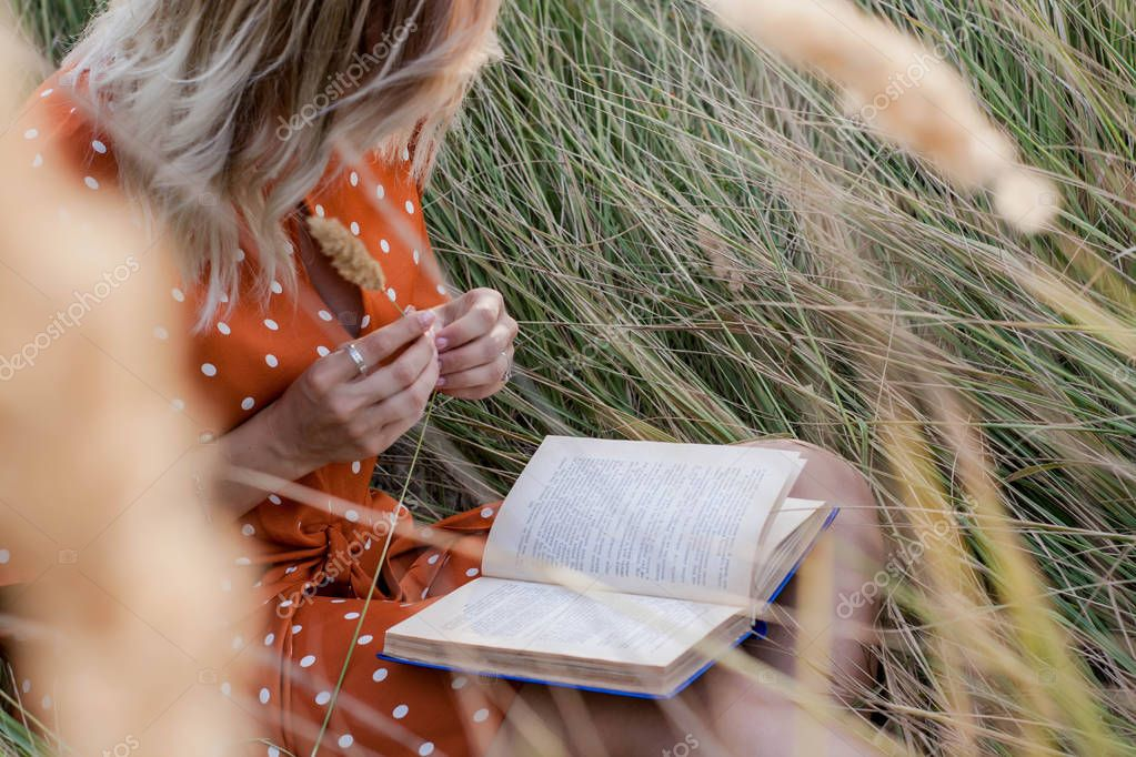 Beautiful happy blonde young woman in field of spikelets and wheat with book on the sunset, in the grass