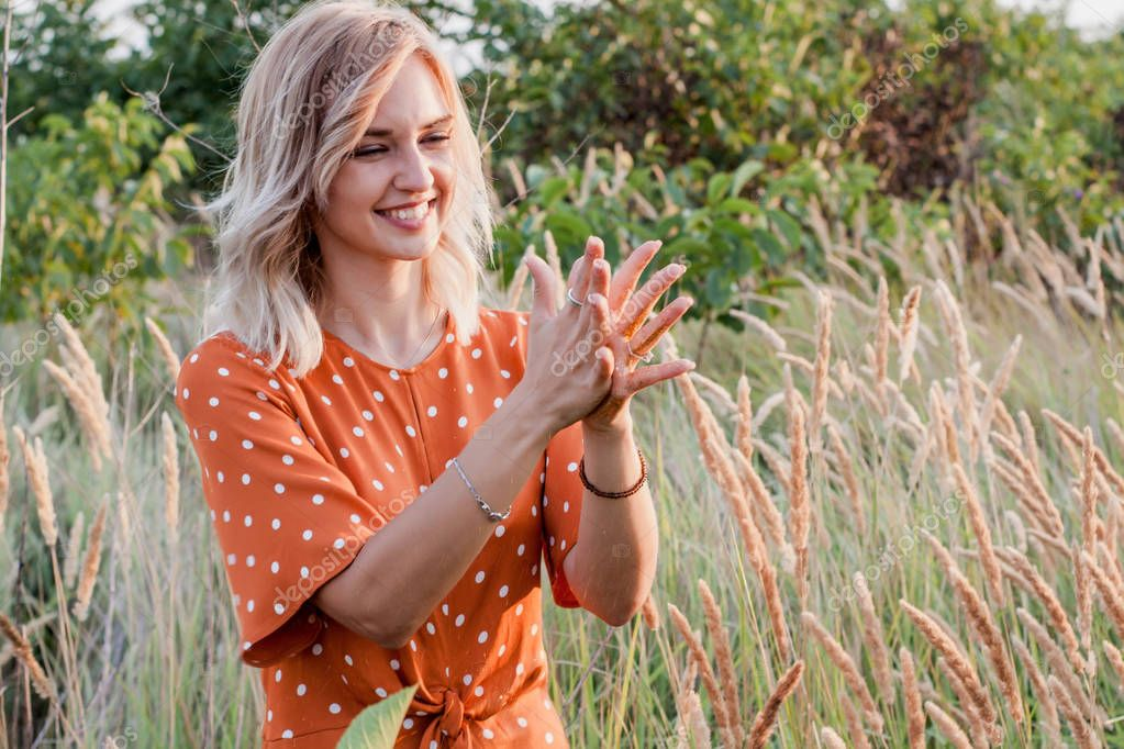 Young blonde woman looking on hands with golden glitters in the field on sunset