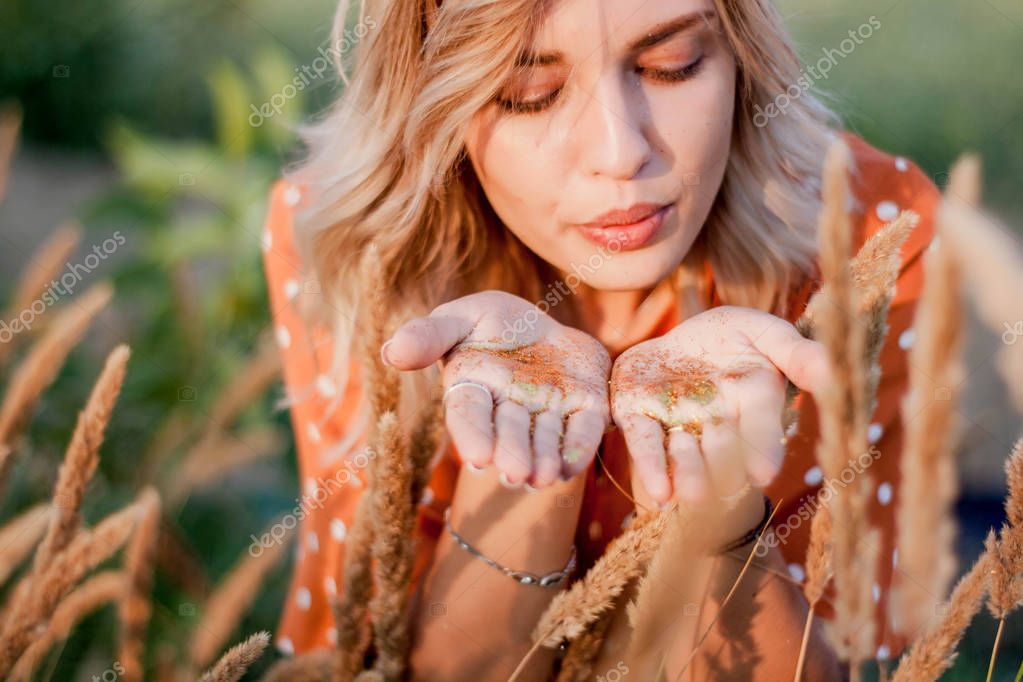 Young blonde woman blowing on hands with golden glitters in the field on sunset