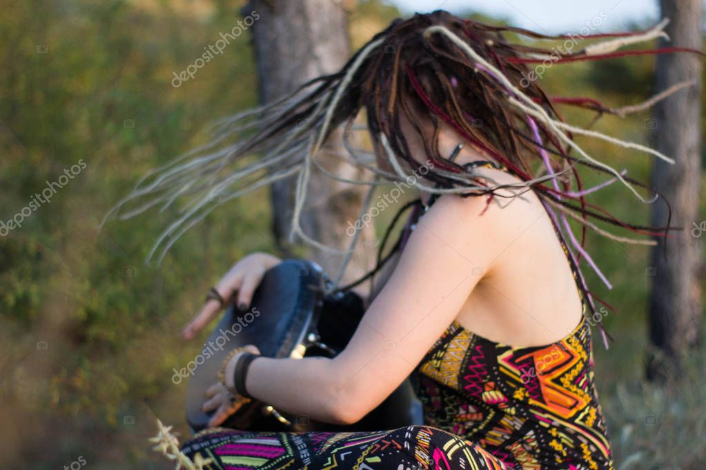 beautiful young woman hippie shaman playing djembe and dancing wild dances at sunset