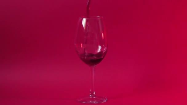 skleničku červeného vína na pozadí červené neonové