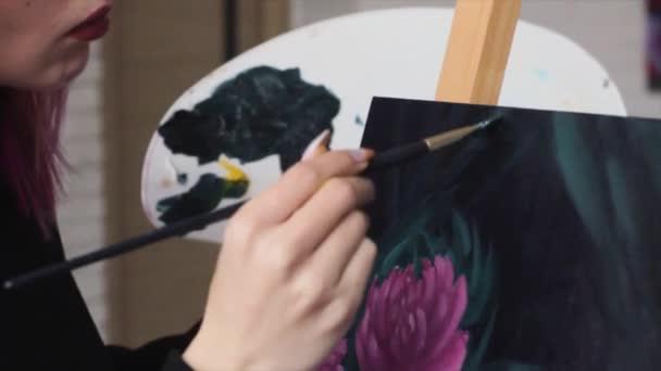 Krásná ženská umělkyně s růžovými vlasy, pracující na výtvarném projektu s paletu v jejích rukou v ateliéru. Mladá žena kreslí obrázek