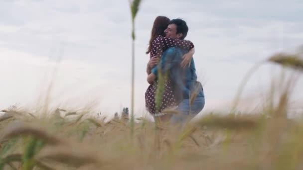 Zamilovaný pár kráčí po poli zelené pšenice a drží se za ruce