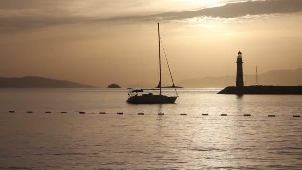 Tengerpart naplementekor. Világítótorony a parton. Tengerparti város Turgutreis és látványos naplementék