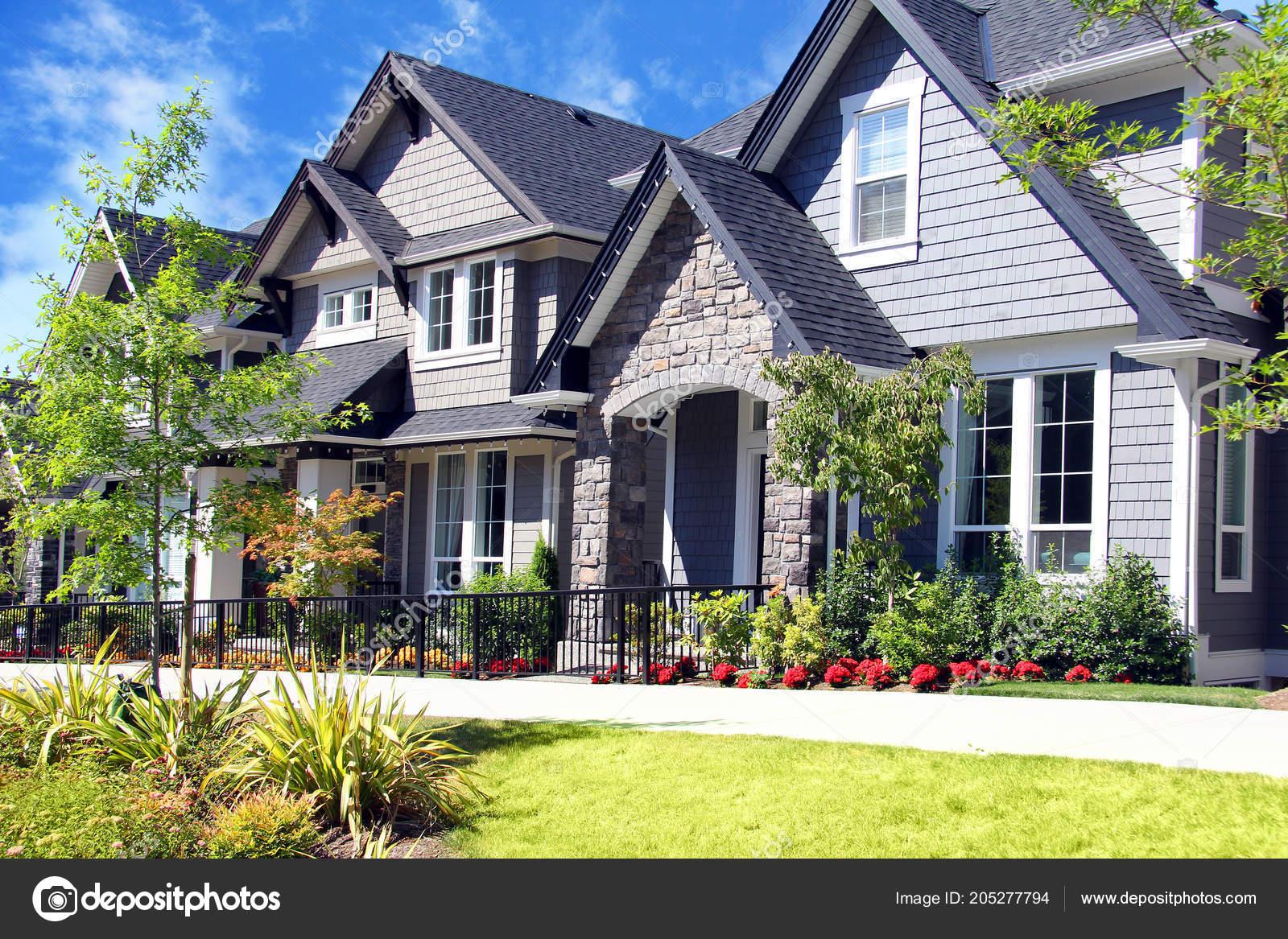 mooie nieuwe tijdloos voorsteden huizen met kleurrijke zomer tuinen