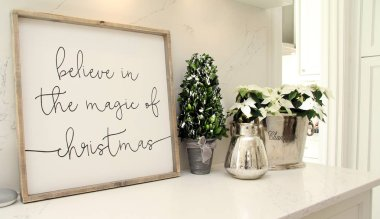 Wooden sign on a kitchen countertop with holiday text: Believe in the Magic of Christmas.