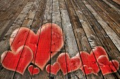 Valentines hearts on a weathered vintage wide plank wooden floor. Valentine love concept for February 14.