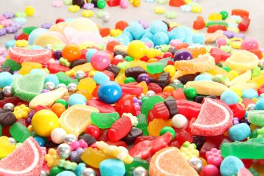 Assorted variety of sweet sugar candies includes lollipops, gummy bears, gum balls and sugar fruit slices. Kids birthday party background.