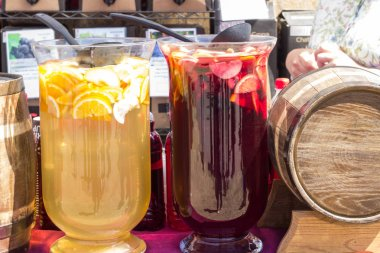 Large glass containers with red and yellow drinks and a wooden barrel with homemade wine