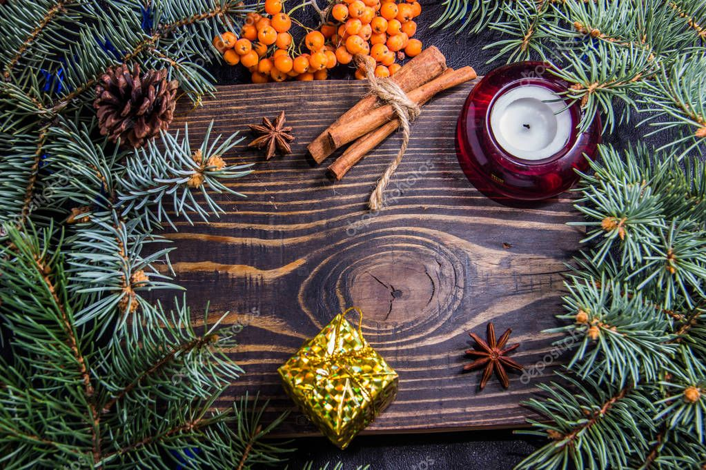 Wooden background with branches of a Christmas tree and a red candle