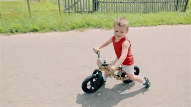 A little boy in a red t-shirt rides a running bike