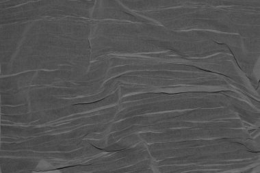 Thin dark grey fabric folded by waves