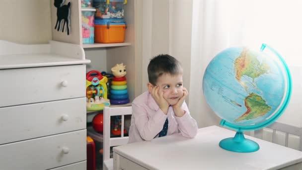 Preschool boy exploring the world on the world globe