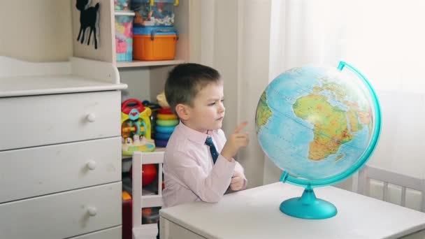 A little boy is looking for a place on the globe where he grew up