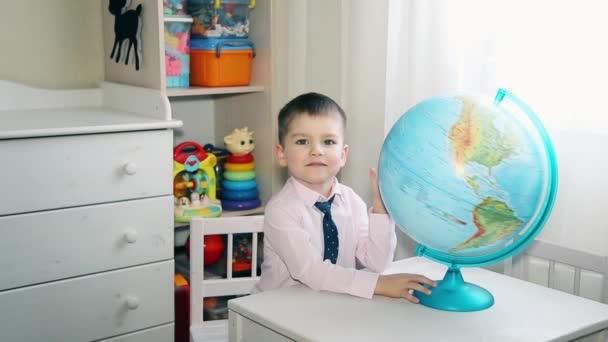 Malý kluk hledá místo na zeměkouli, kde vyrůstal