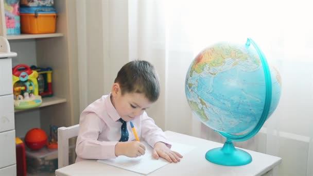 A gyermek tanulmányok a földön, és jegyzeteket írja a notebook