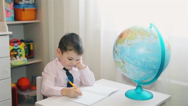The child studies the planet Earth and writes notes in a notebook
