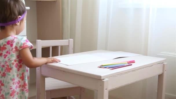 Kislány a gyerekszobában virágos ruhában tanul rajzolni barna ceruzával Hd 1080
