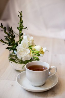 cup of tea on a saucer and a white freesia flower