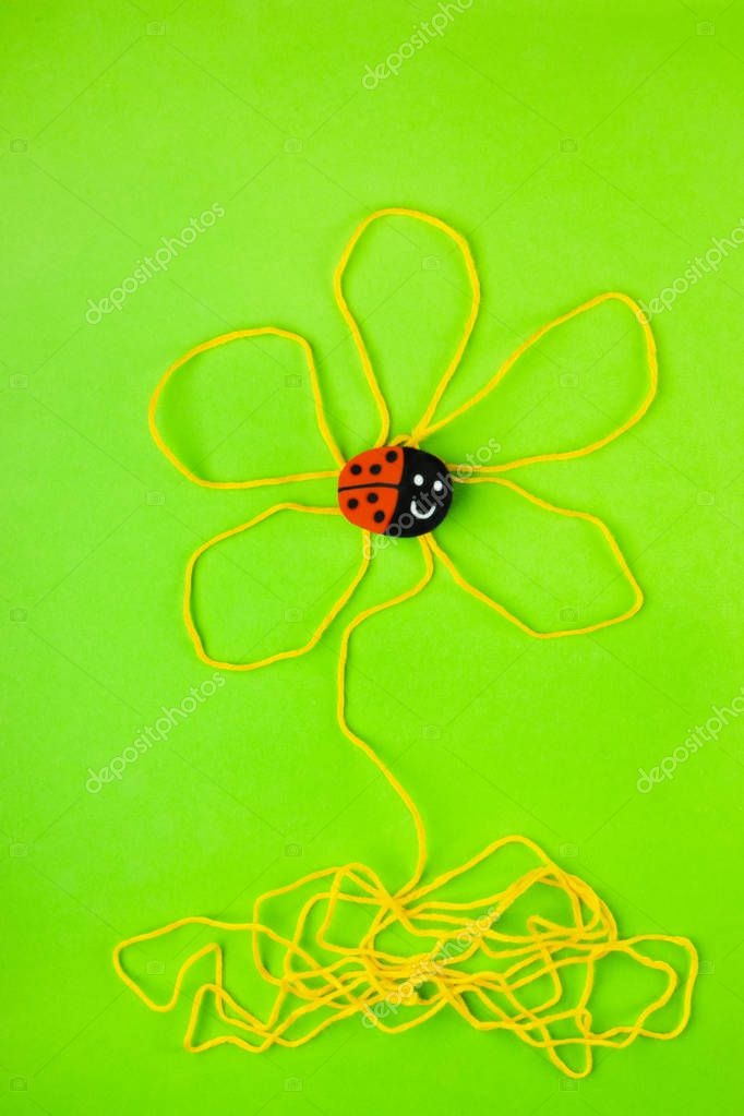 One eraser shaped like a ladybird on a stylised flower made with yellow thread , the background is green , fantasy has no limit