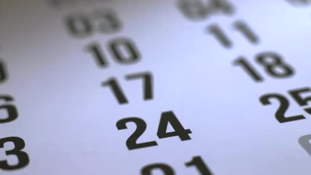 Marking with a cross number 24 on a calendar with a red pen