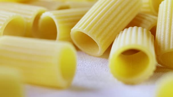 Italian pasta called mezzi rigatoni on white cotton cloth ,tube-shaped pasta with ridges down their lenght ,rack focus